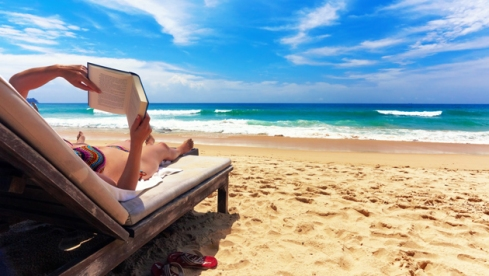 woman-reading-book-at-beach